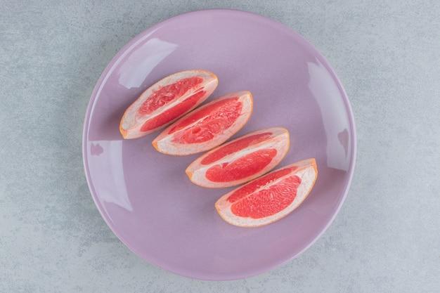 Plasterki grejpfruta na talerzu na marmurze