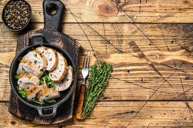 Plasterki grillowanego stek z polędwicy wieprzowej na patelni.