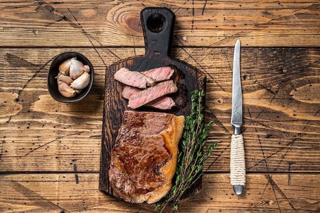 Plasterki grillowany stek wołowy new york strip lub rostbef na desce. drewniane tła. widok z góry.
