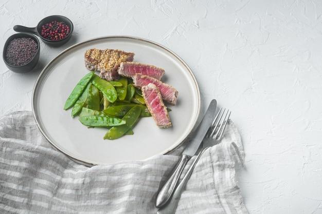 Plasterki grillowany stek z tuńczyka w sosie sezamowo-sojowym z cebulką dymką i groszkiem cukrowym, na talerzu, na białym kamiennym tle, z copyspace i miejscem na tekst