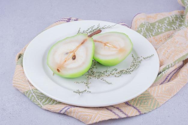 Plasterki gruszki z ziołami na białym talerzu