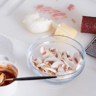 Plasterki grzybów; ser; masło; szynka; sos i salami na desce do krojenia