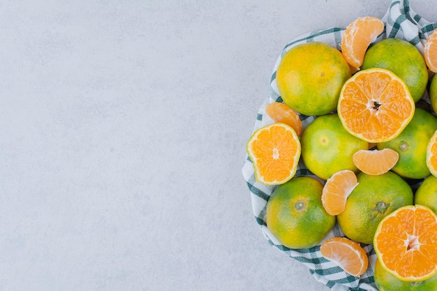 Plasterki i całe mandarynki w obrusie na białym tle. zdjęcie wysokiej jakości