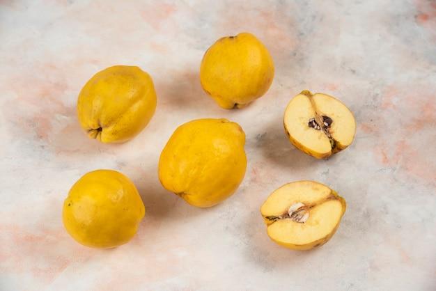 Plasterki i całe świeże owoce pigwy na marmurowym stole.