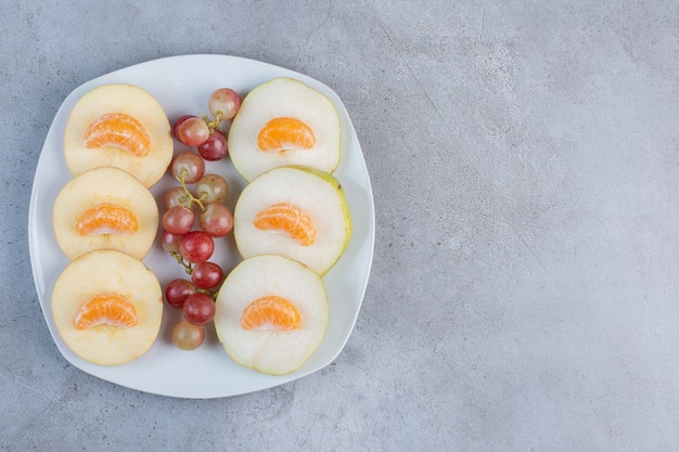 Plasterki jabłek, gruszek, mandarynek i winogron na talerzu na tle marmuru.