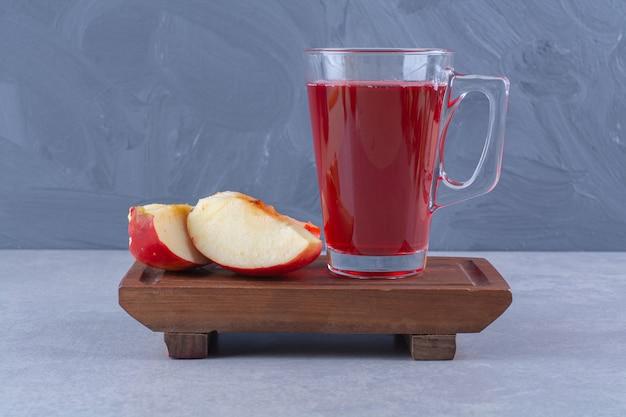 Plasterki jabłka i szklankę soku wiśniowego na drewnianym talerzu na marmurowym stole.