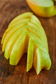 Plasterki jabłka na drewnianej desce do krojenia, z bliska.