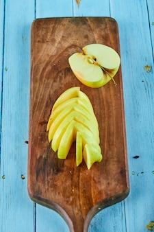 Plasterki jabłka na drewnianej desce do krojenia.