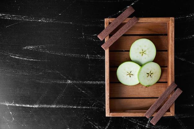 Plasterki jabłka na drewnianej tacy.