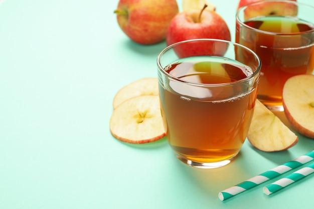 Plasterki jabłka, słomki i szklanki soku jabłkowego na mięcie