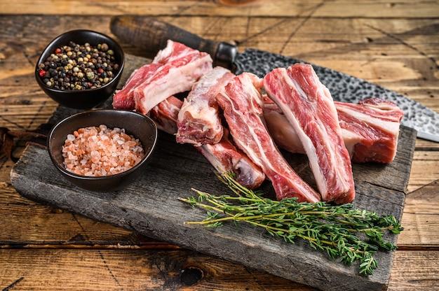 Plasterki jagnięciny krótkie, zapasowe żeberka, surowe mięso na drewnianej desce do krojenia