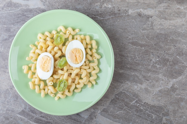 Plasterki jajka i makaron na zielonym talerzu.