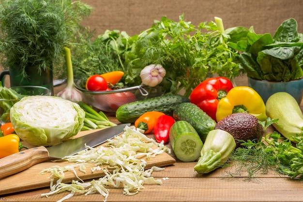 Plasterki kapusty, nóż kuchenny na desce do krojenia. warzywa i koperek, liście szpinaku i kolendra na stole. drewniane tło.