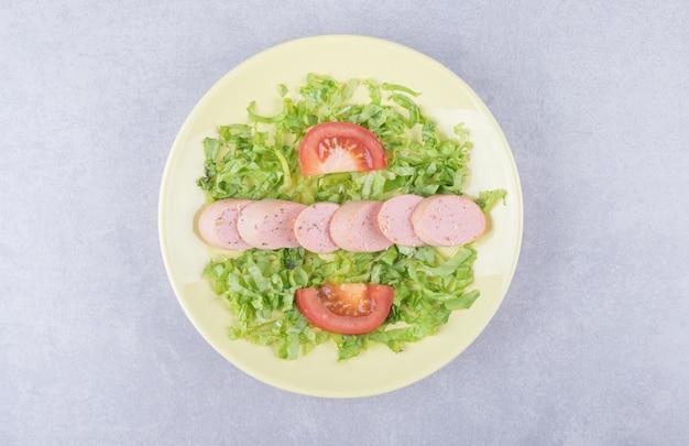 Plasterki kiełbasek i pomidorów na żółtym talerzu.