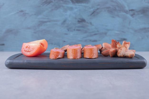 Plasterki kiełbasek z pomidorami na ciemnej desce.