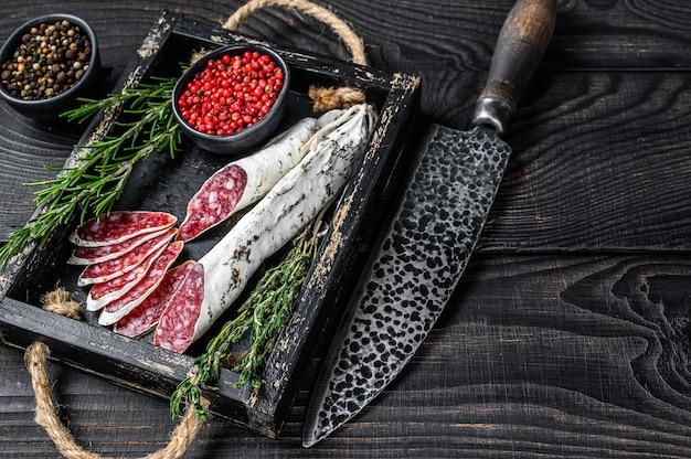 Plasterki kiełbasy fuet salami z tymiankiem i rozmarynem na drewnianej tacy.