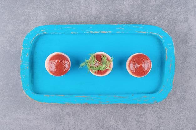 Plasterki kiełbasy z keczupem na niebieskiej desce