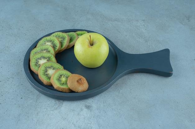 Plasterki kiwi i jabłka na patelni, na marmurowym tle. zdjęcie wysokiej jakości