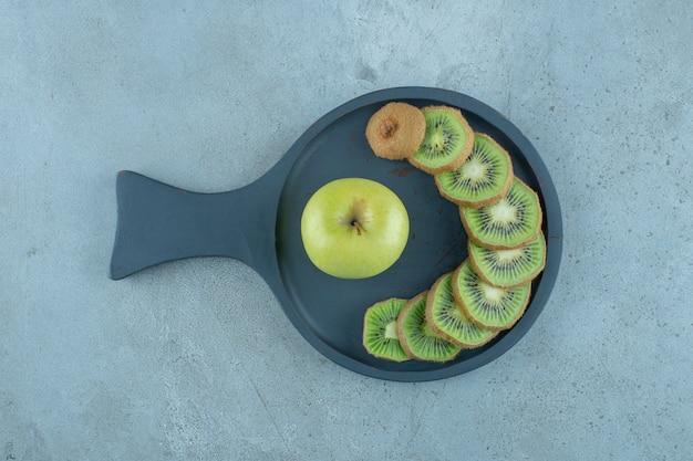 Plasterki kiwi i jabłka na patelni, na marmurowym tle.