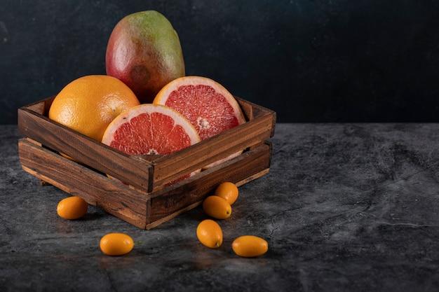 Plasterki kiwi, kinkanów, pomarańczy i grejpfruta w drewnianej tacy na ciemnym marmurze