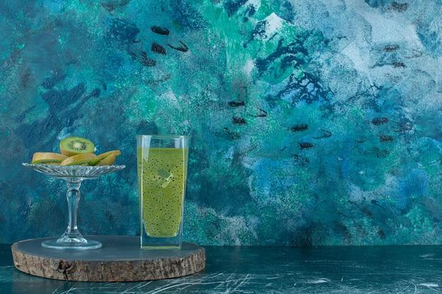 Plasterki kiwi obok szklanki smoothie kiwi na desce, na marmurowym tle.