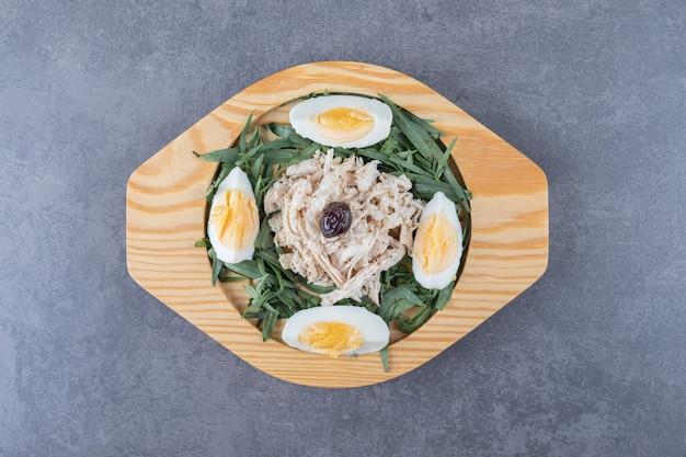 Plasterki kurczaka z jajkami i estragonem na drewnianym talerzu.