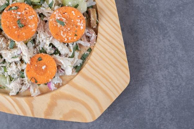 Plasterki kurczaka z marchewką na drewnianym talerzu.