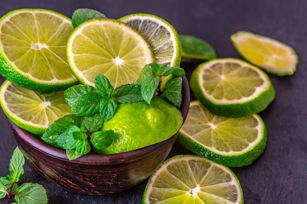 Plasterki limonki z miętą na ciemnym stole. dieta detoksykacyjna.