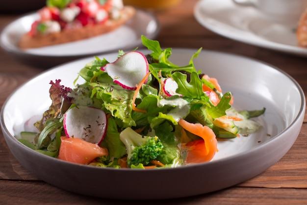 Plasterki łososia z sałatką ze świeżych warzyw na talerzu.