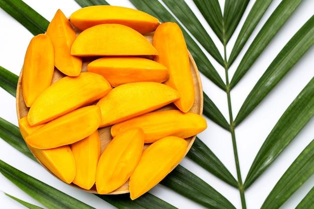 Plasterki mango na drewnianym talerzu na liściach tropikalnych palm. widok z góry