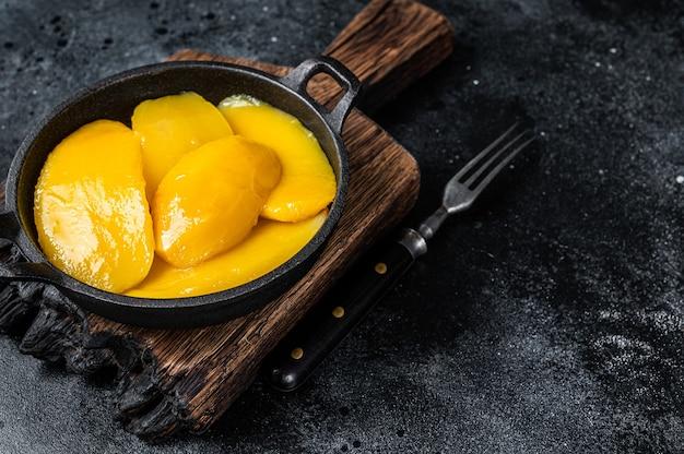 Plasterki mango w puszkach w misce czarne tło.