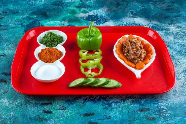 Plasterki marchewki, fasoli i warzyw na talerzu na tacy, na niebieskim stole.