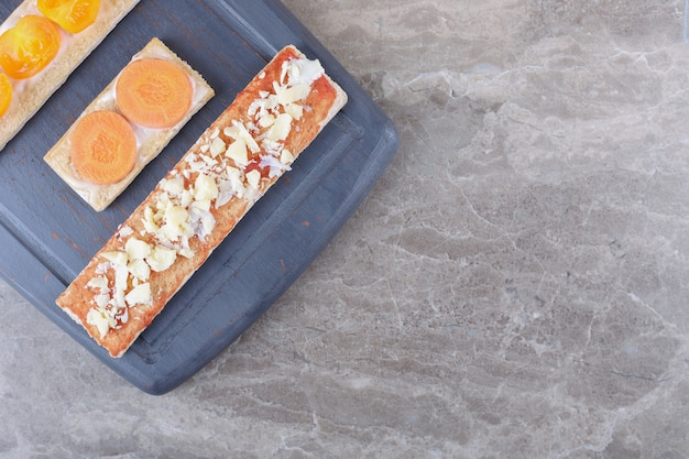 Plasterki marchewki, sera i pomidorów na chrupiącym pieczywie na drewnianej tacy, na marmurowej powierzchni