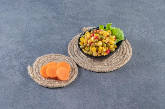 Plasterki marchewki, trójnóg i miska sałatki kukurydzianej, na marmurowym tle.