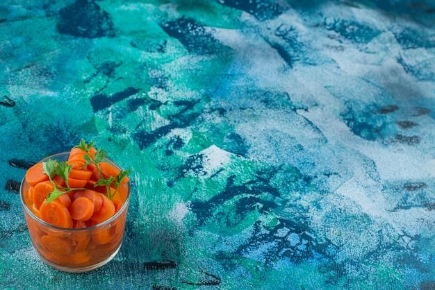 Plasterki marchewki w szklance, na niebieskim stole.