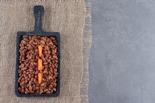 Plasterki marchwi na desce fasoli na jutowej serwetce na niebieskiej powierzchni