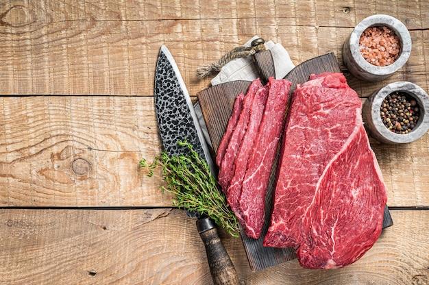 Plasterki marmuru surowego mięsa wołowego na drewnianej desce do krojenia. drewniane tła. widok z góry. skopiuj miejsce.