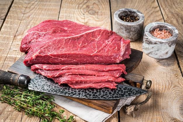 Plasterki marmuru surowego mięsa wołowego na drewnianej desce do krojenia. drewniane tła. widok z góry.
