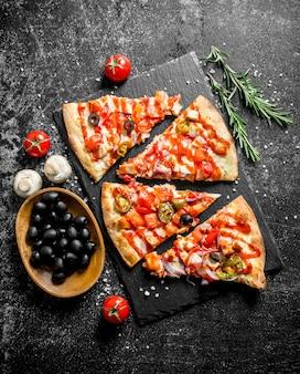 Plasterki meksykańskiej pizzy z pomidorami, oliwkami i rozmarynem na ciemnym stole rustykalnym