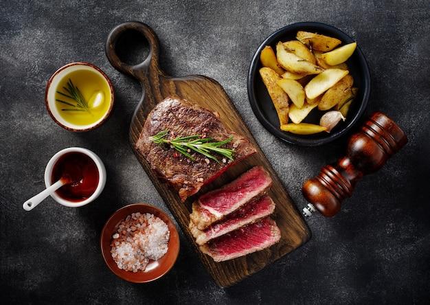 Plasterki mięsa z grilla stek nowy jork rostbef z sosem i ziemniakami na desce na szarym tle. widok z góry.