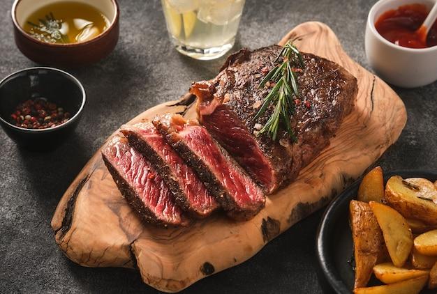 Plasterki mięsa z grilla stek nowy jork rostbef z sosem i ziemniakami na desce na szarym tle.