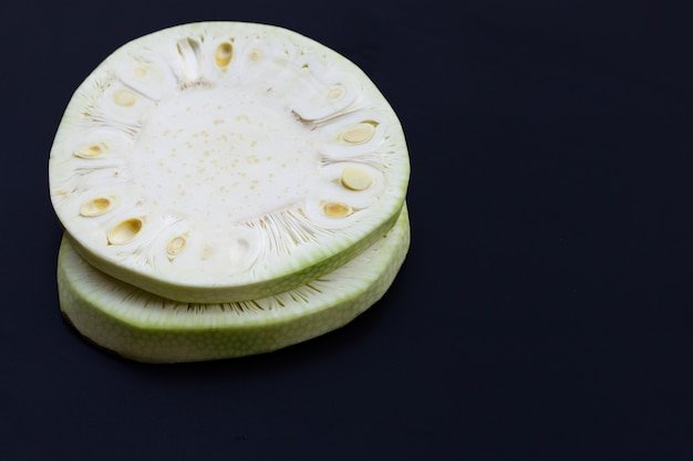 Plasterki młodego jackfruit na ciemnej ścianie. skopiuj miejsce