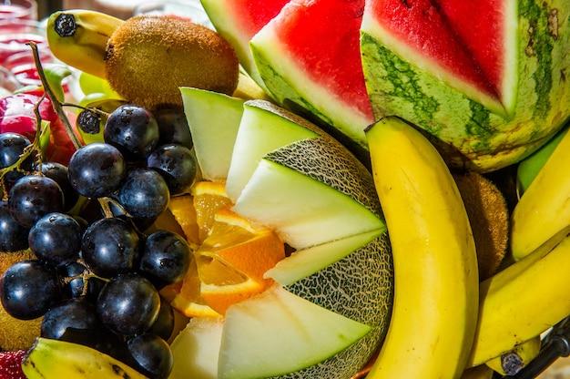 Plasterki na białym tle owoców tropikalnych. świeże egzotyczne owoce pokrojone na pół (marakuja, kiwi, mangostan, ananas, smoczy owoc) z rzędu na białym tle ze ścieżką przycinającą