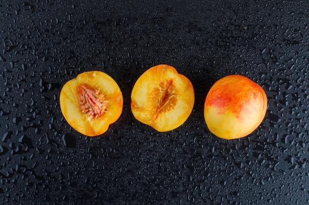 Plasterki nektarynki na ciemnoszarym stole, płaskie.