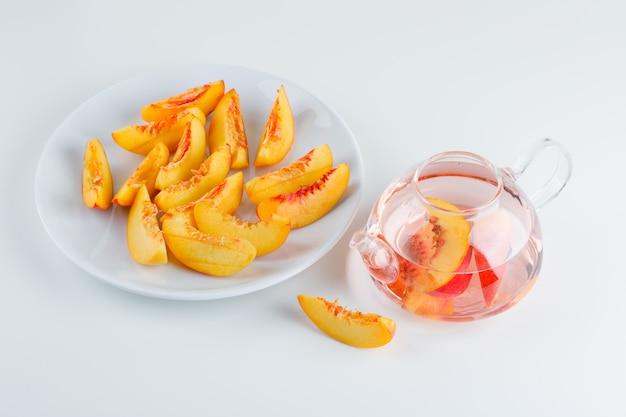 Plasterki nektarynki na talerzu z napojem pod wysokim kątem na białej powierzchni
