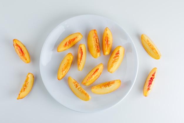 Plasterki nektarynki w talerzu na białej powierzchni. leżał płasko.