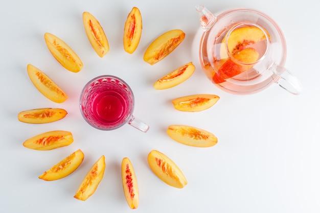 Plasterki nektarynki z letnim napojem na białym stole, widok z góry.