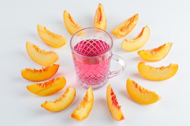 Plasterki nektarynki z letnim napojem na białym stole, wysoki kąt widzenia.