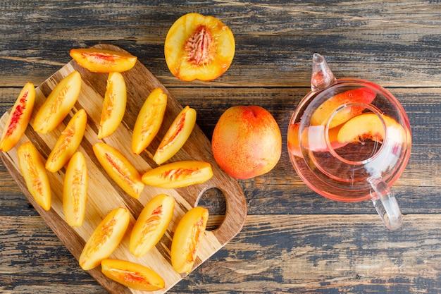 Plasterki nektarynki z napojem na stole drewniane i deska do krojenia, widok z góry.