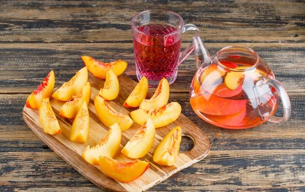 Plasterki nektarynki z widokiem na napój wysoki kąt na stole drewniane i deska do krojenia